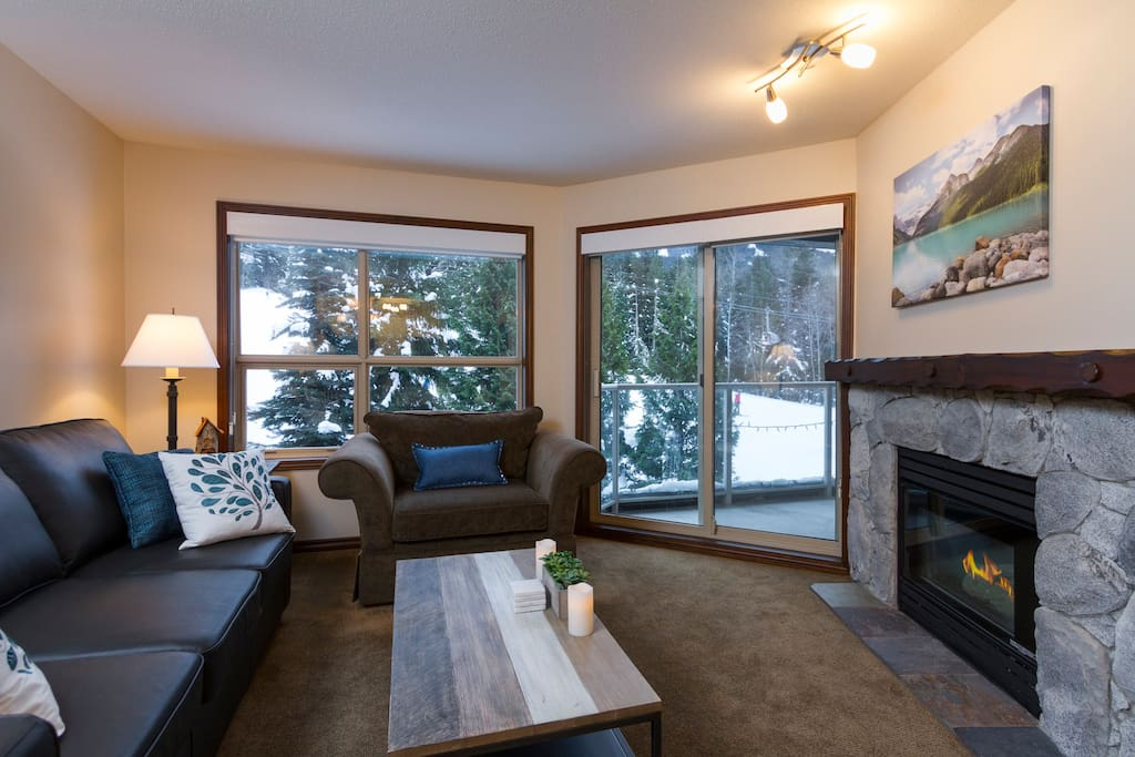Living room with a cozy gas fireplace overlooking the slopes of Blackcomb Mountain