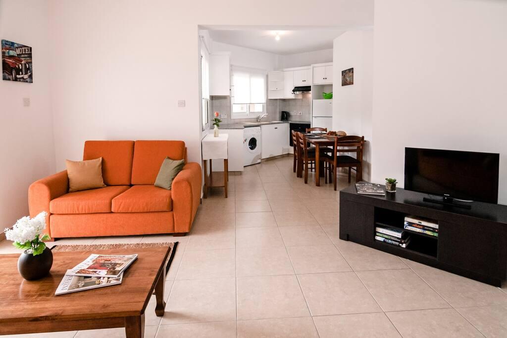 Односпальный апартамент: Гостиная  и вид кухни / столовой дальним планом.
