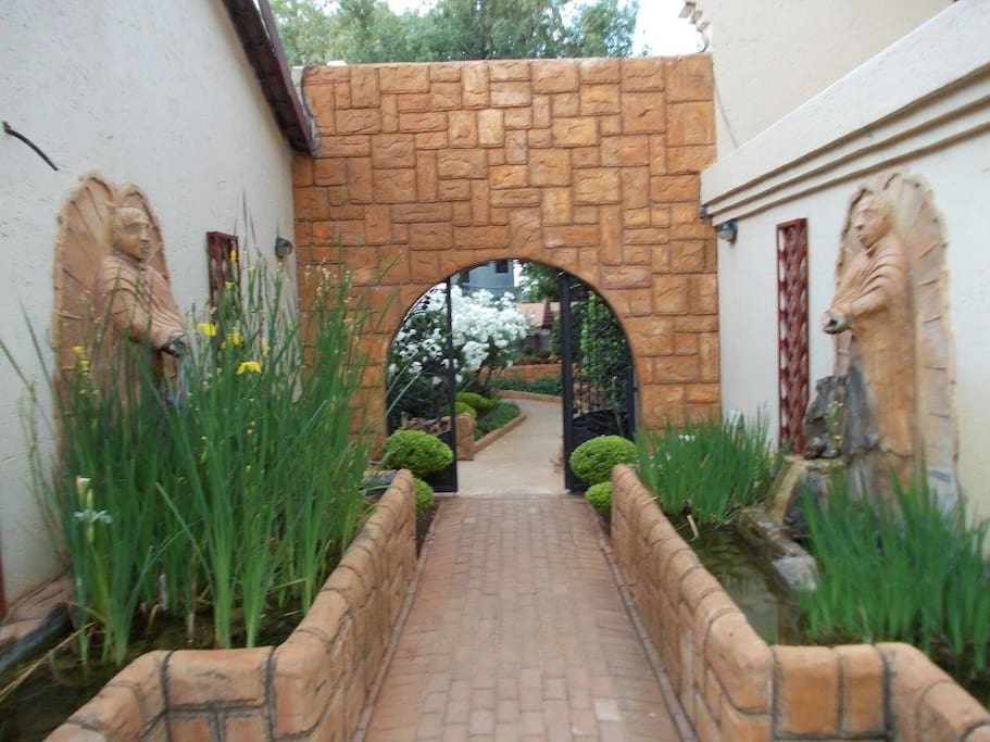 Entrance from the parking to some of the rooms, bar, swimming pool, dining area, fish pond and a beautiful garden