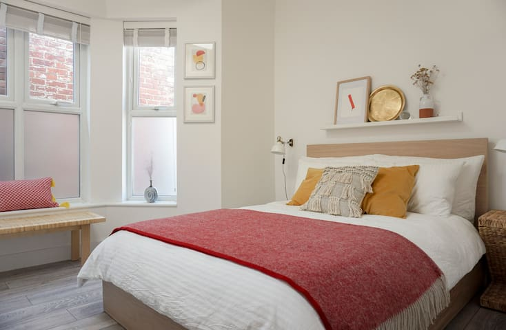 Bedroom - Decorated with warm, and inviting colors and textures. Featuring a UK double bed (135cm x 190cm) with crisp, clean sheets and fluffy pillows and cushions. Accented with original artwork prints, studio ceramics.