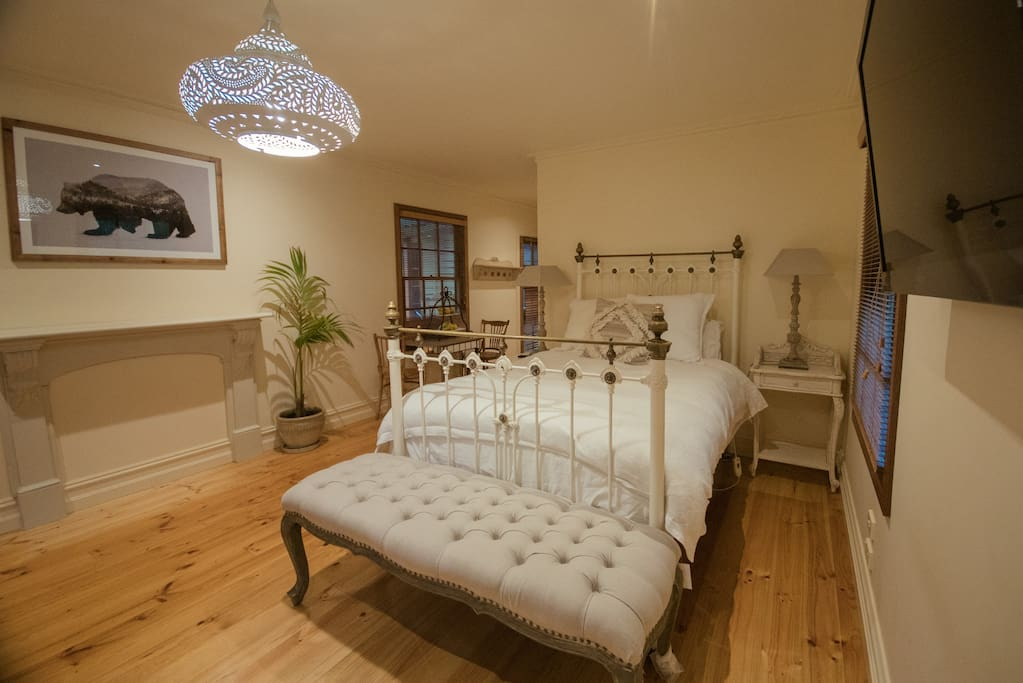 Large spacious Master bedroom with queen bed . A TV on the wall , to lie back and enjoy the evening or wake up and watch the news with the click of the remote