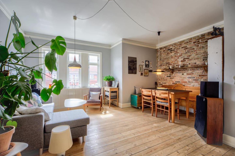Stor, rummelig stue med spisekrog, sofa og lille arbejdsbord til at sidde med computeren. Bemærk at sofaen er skiftet ud med en smallere, men længere.