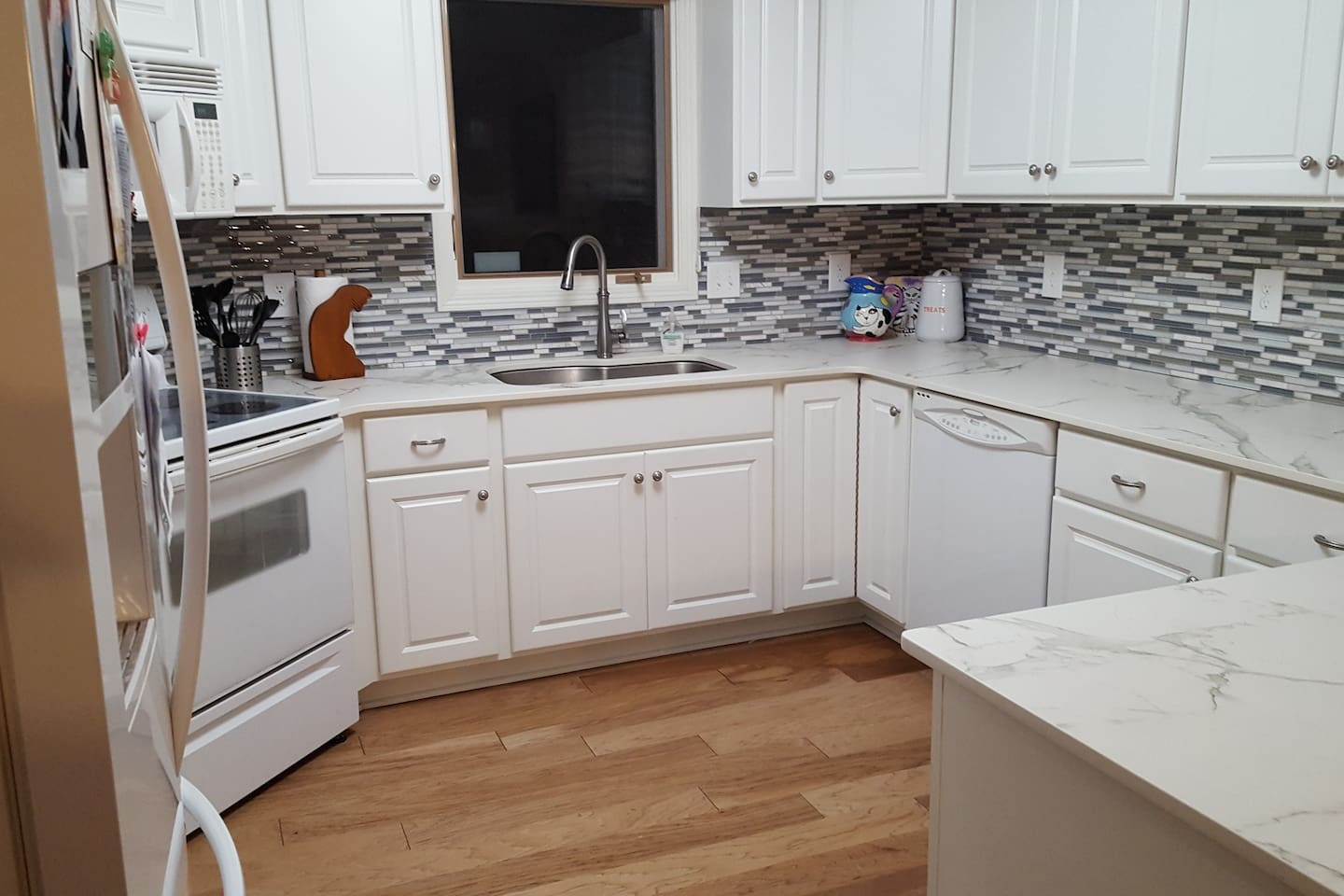 New range and dishwasher, freshly painted lower cabinets, 30 cf refridgerator. Seperate pantry, breakfast bar and large dining room table.