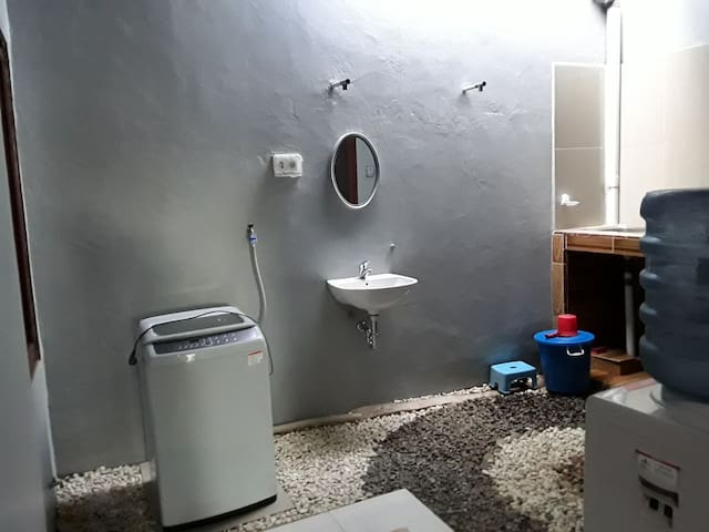 Dapur dilengkapi mesin cuci otomatis dengan kapasitas 7kg, wastafel, tempat cuci piring, dan cermin.  The kitchen is furnished with an automatic washing machine (7kg capacity), a wash basin, a kitchen sink, and a mirror.