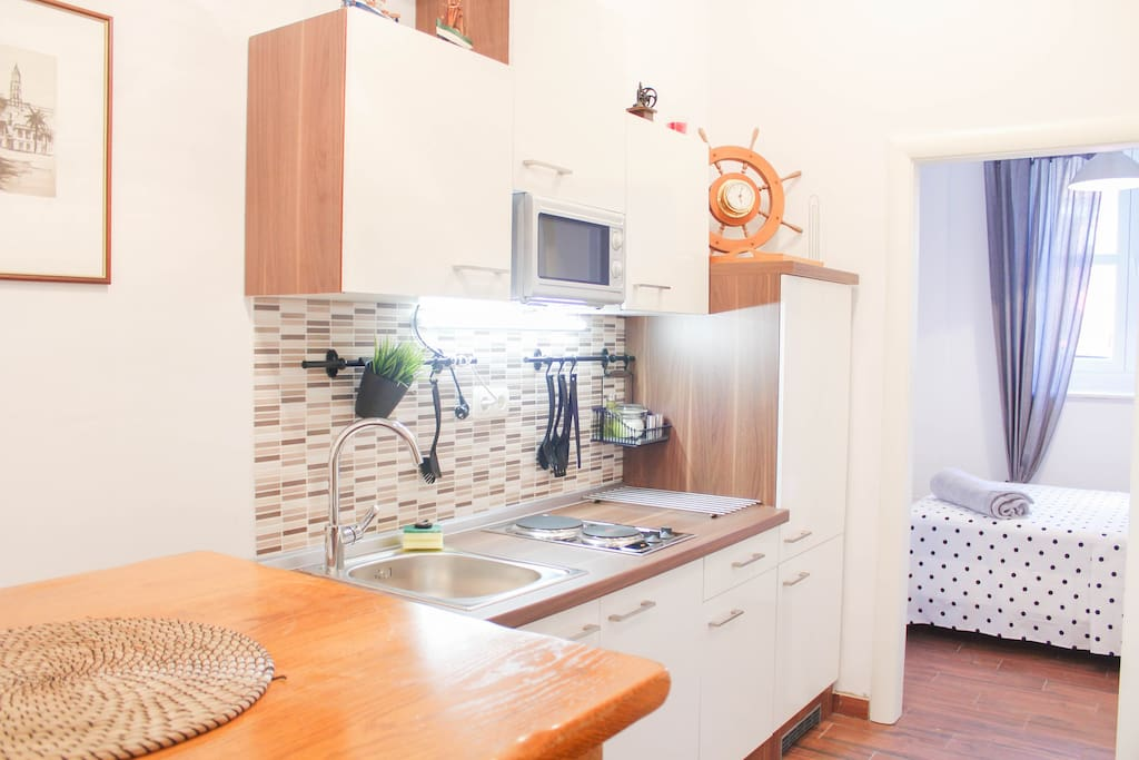 Kitchen with microwave, electric kettle, stove and fridge