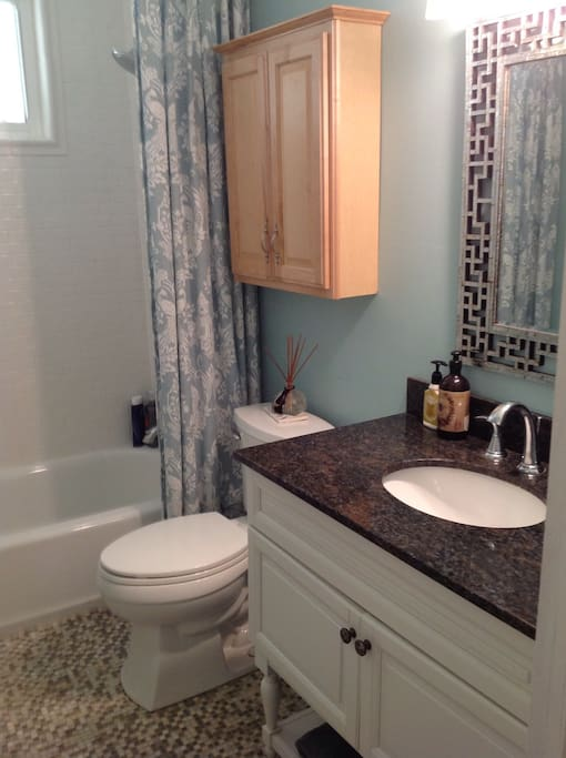 The bath features marble tiles and marble vanity and is stocked with luxury bath towels