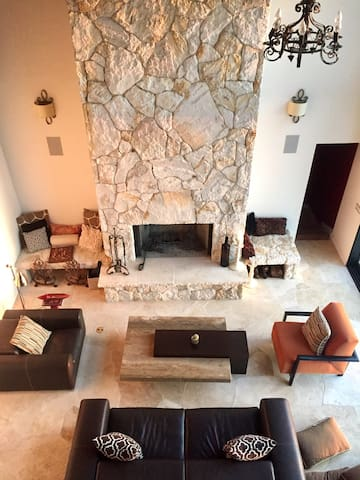 Livingroom surrorrounded by wrap-around balcony and 28' ceilings, wood burning fireplace. Wall of sliding glass to open up to the outside!