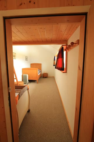 Schlafzimmer mit Einzelbett und Reisebabybett
