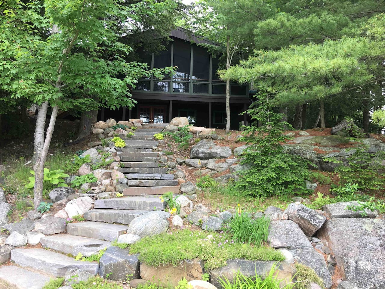 Classic Muskoka cottage, west-facing for year-round sunsets. Stone steps lead to small, private beach.