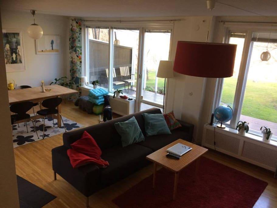 Vardagsrum med soffa, tv och öppen spis. Fönster mot gavel och baksida.