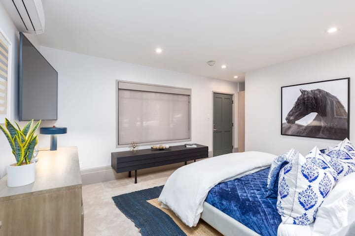 Second master bedroom with king size bed, large flat screen tv, private entrance, and private bathroom
