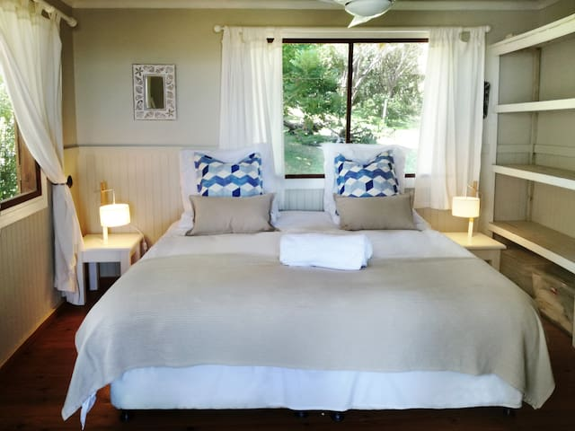 King size bed in downstairs bedroom.  with large airy windows.   Double doors lead onto the deck with a sea view.