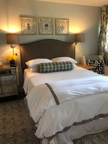 Light filled bedroom with luxury JP Rogers luxury bed, and luxury linens, TV with (Netflix), comfy upholstered chair for reading or watching TV, desk/make up vanity complete with lighted make up mirror and chair