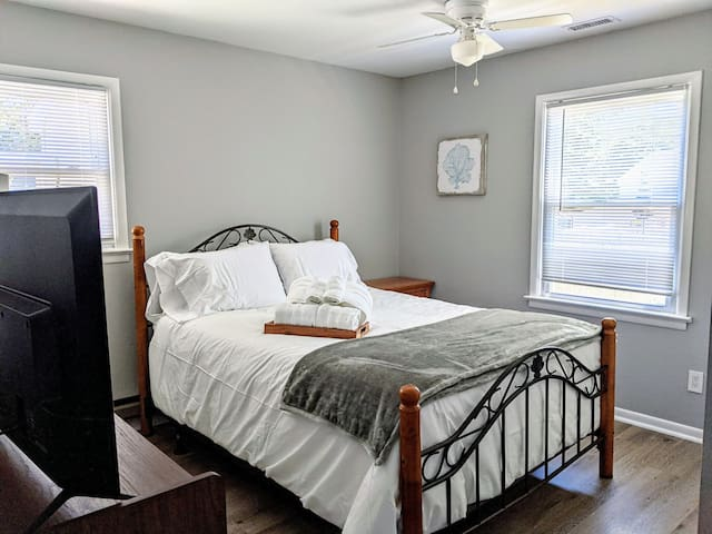 Tastefully contains a luxurious queen bed, roomy mid century dresser, smart tv, and ceiling fan.