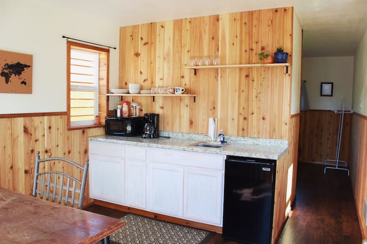 Kitchen area includes microwave, coffee pot, single burner hot plate and a small refrigerator. As well as dishes & utensils.