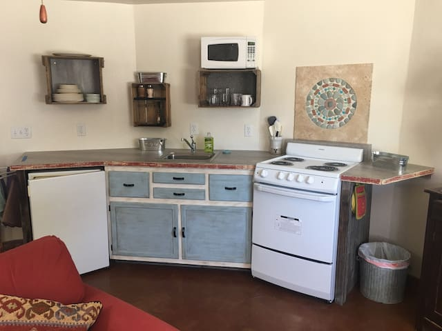 Your kitchen with refrigerator, range, microwave and sink. All the pots and pans silverware, plates and everything else you need.
