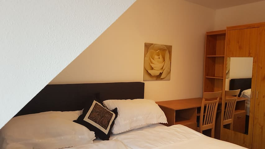 Bed room 1 with a double bed, which can also be separated. The room also contains a wardrobe and a desk.