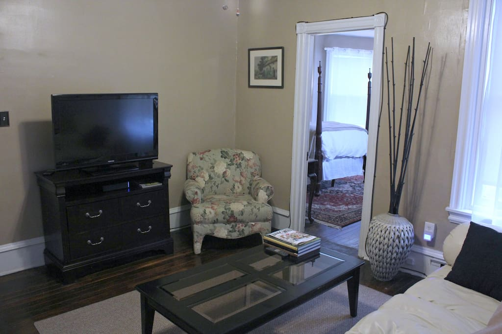 """Bright living room offers oversized windows with shades, leather couch, 37"""" flat screen tv, comfortable chair."""