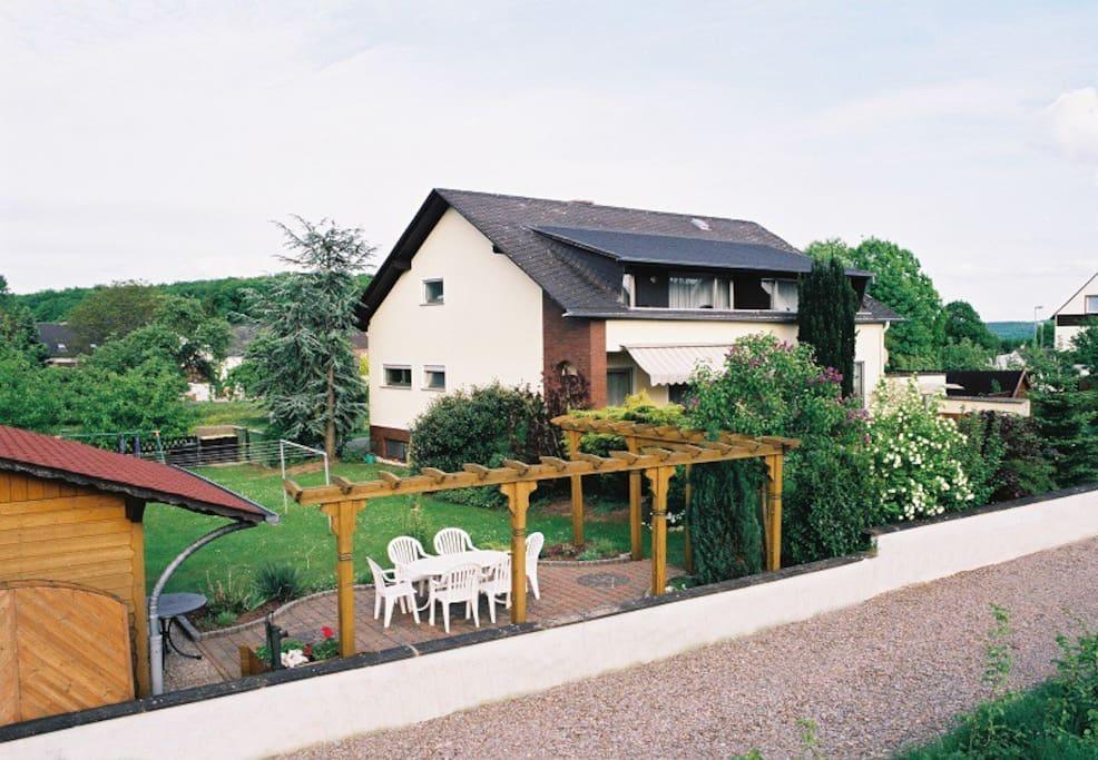 Rückansicht unseres Hauses mit großem Garten. Die Wohnung befindet sich im 1. OG mit Balkon.
