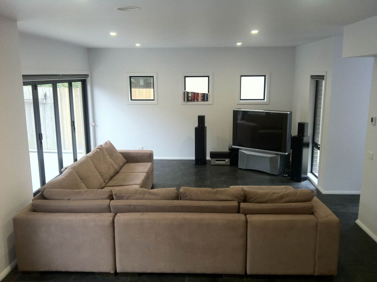 Living Room with large corner couch, 5-panel bifold doors, and cable tv
