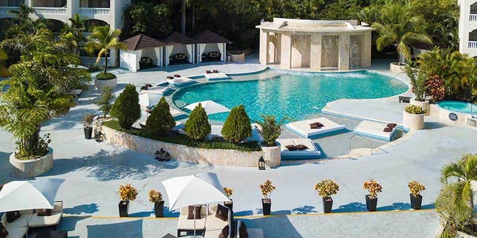Exclusive poolside comfort with waterfall, cabana and poolside chaise.