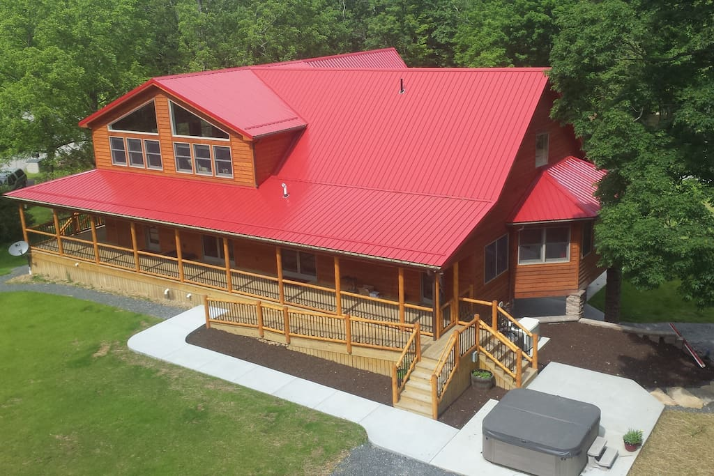 Rear side of chalet with hot tub, handicap accessible ramp, and covered porch