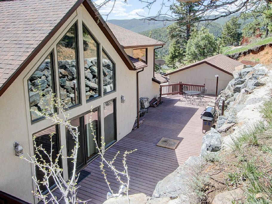 Secluded 900 sqft deck at back of house with barbeque and patio table.