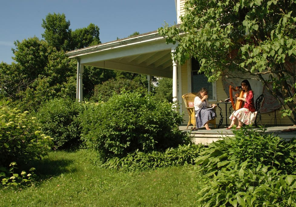 Guests enjoy the porch with tea and harp playing