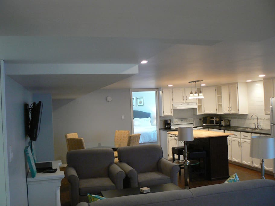 Open living space with kitchen, island and appliances, dining and living room.