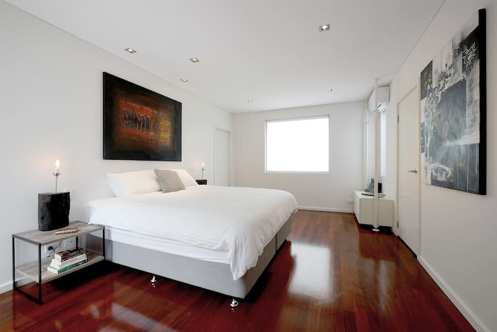 Master bedroom with two queen size beds and walk-in wardrobe