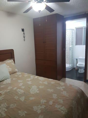 """Recámara Principal con  cama matrimonial, cama individual y baño privadocompleto, closet, TV de 32"""", aire acondicionado y ventilador."""