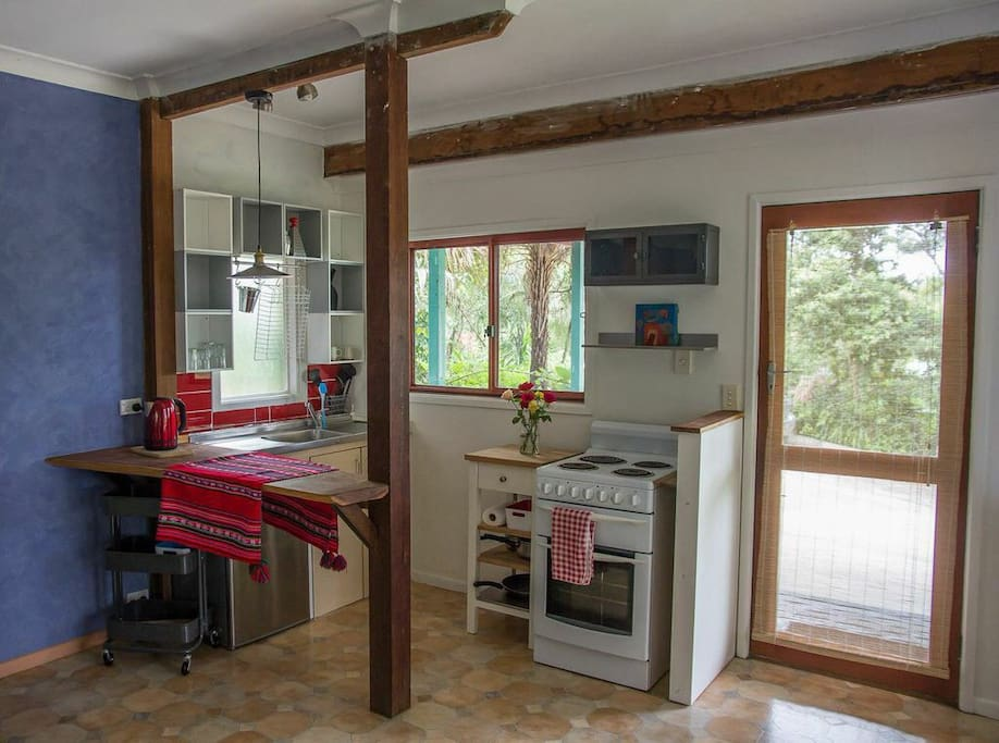 Funky little kitchen with stove, fridge, timber bench and plenty of light