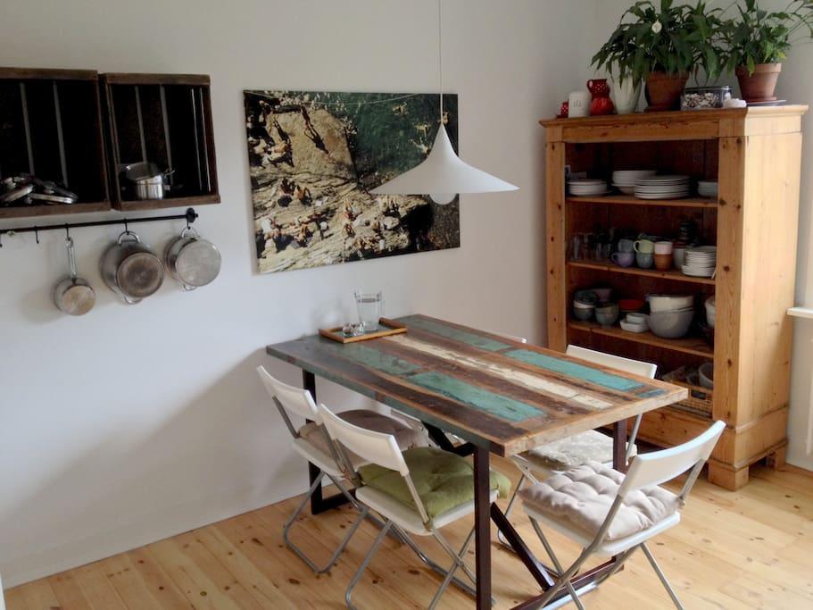 Lichtdurchflutete Küche mit Blick in den grünen Innenhof mit Schrebergärten