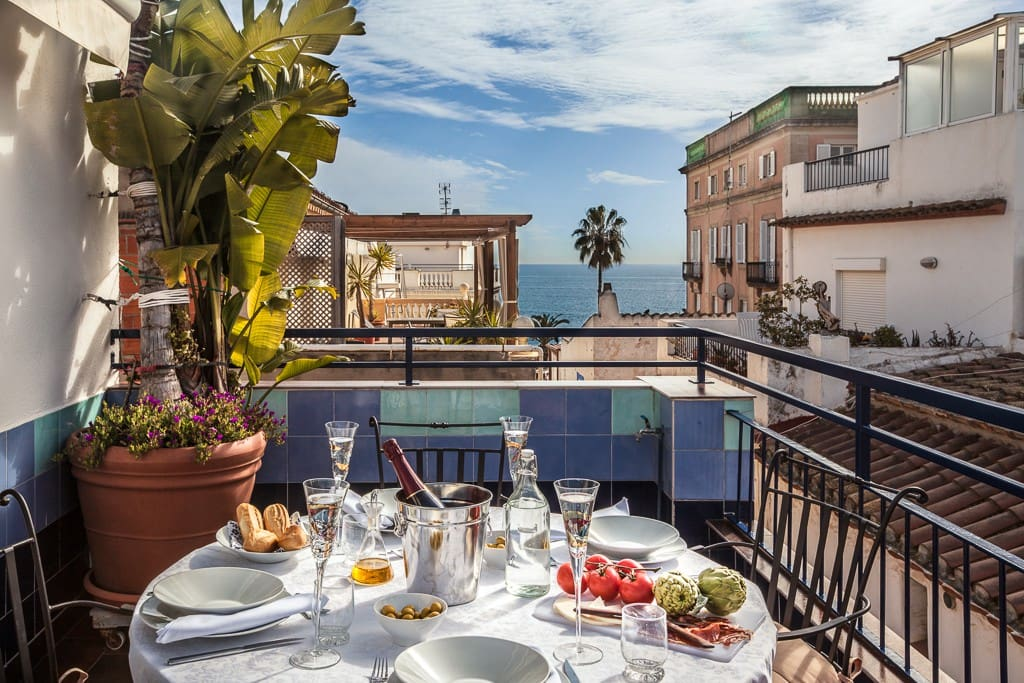 Comfortable seating for 4 and a large awning are located on the dining terrace. Sea View Sitges Holiday Rental Apartment,  Beach Vacation Accommodation. Tourist License: HUTB-006157.