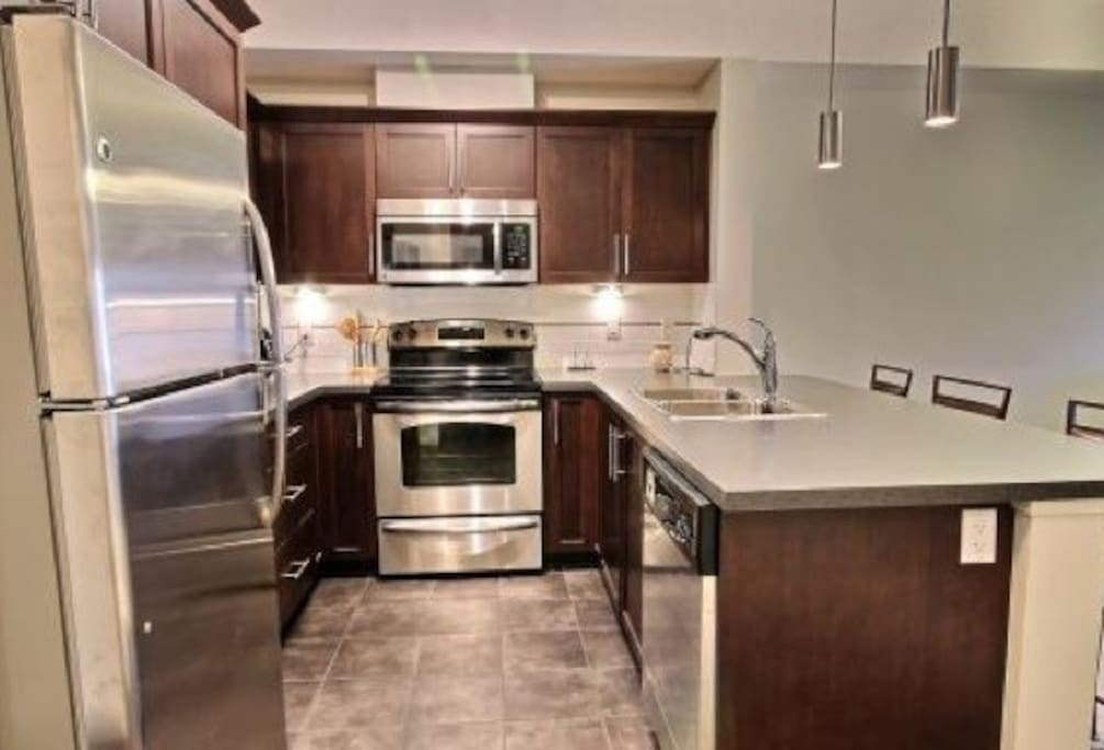 Upgraded kitchen features stainless steel appliances, microwave, tassimo coffee maker, and blender.