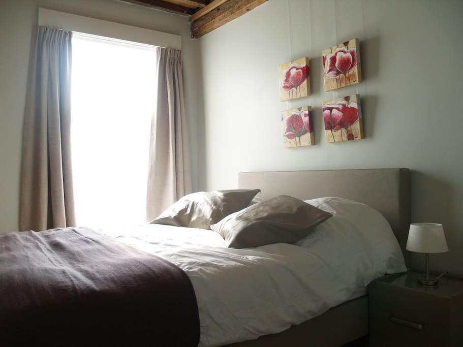 This is our first bedroom, with double bed with boxspring (Queensize), this room offers a view over a beautifully landscaped English-style garden and has all necessary comfort: sun blinds, safe, reading corner, large louvre-style cupboards, suitcase stand