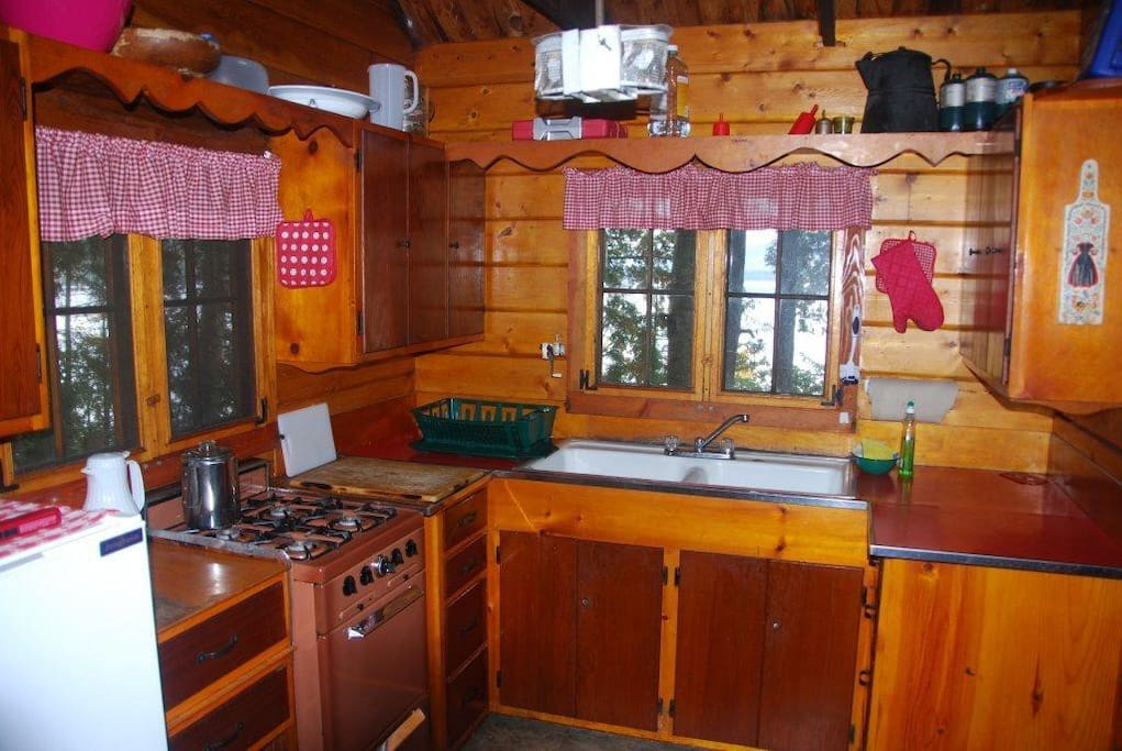 Kitchen with refrigerator and propane range.