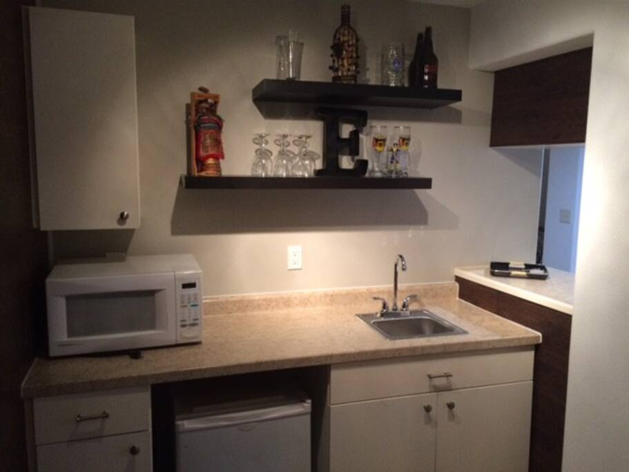 """Wet bar area. Small refrigerator, dishes, and microwave. Small """"kitchen"""" area in the basement."""