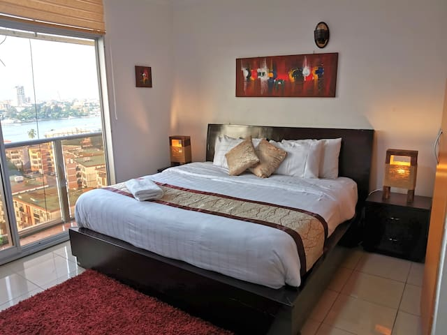 King sized bed with full linens, comfortable pillows and a balcony right off the bedroom overlooking Victoria Island.