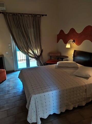 Spacious double room with private bathroom with shower and balcony with sea view . Room includes a TV & a small fridge for your personal items.