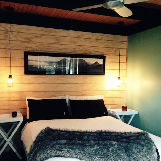 Queen bed in extra large bedroom that opens onto a private deck.
