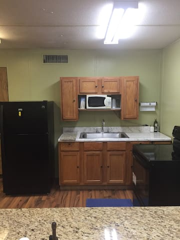 A kitchen with full refrigerator, microwave, sink, stove and oven.