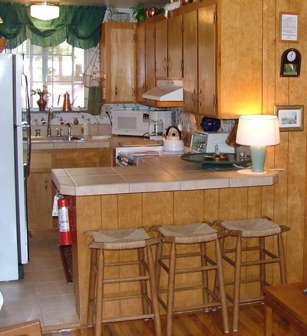 Convenient and well equipped knotty pine kitchen with breakfast bar.