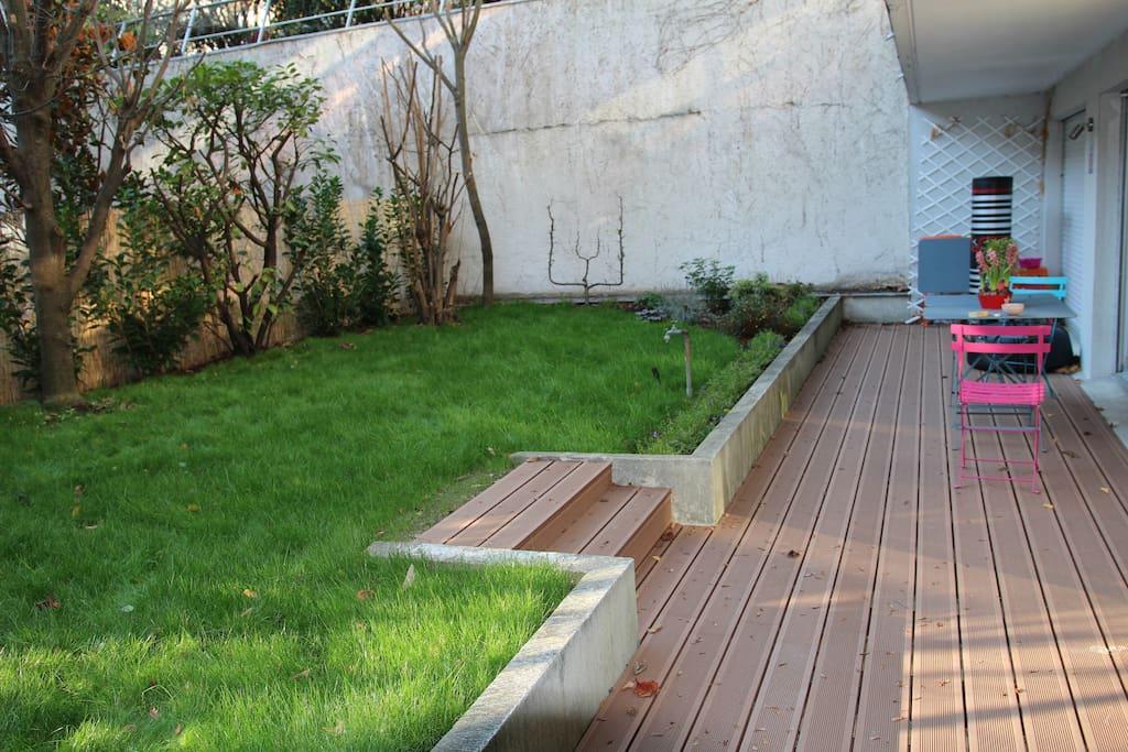 Jardin de 100m2 avec terrasse en bois.