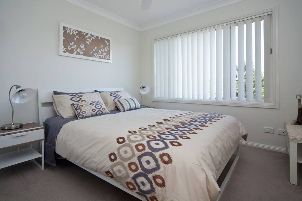 Bedroom with large picture window and verticals for privacy