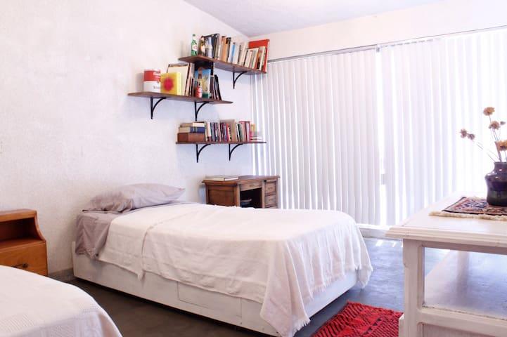 Hermosa habitación con dos camas y balcón.