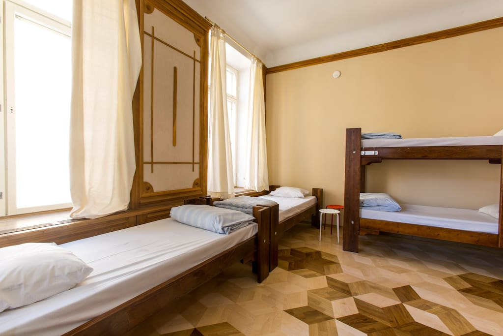 The room has 4 bunks and 2 single beds made of sturdy wood