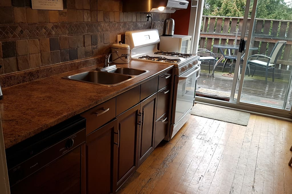 Bright kitchen with gas stove and dishwasher