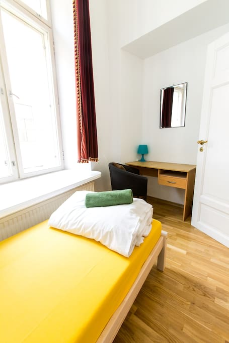 Bright single room with great street view and work desk.