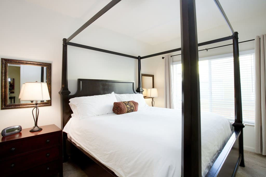 Master bedroom w/ solid wood king canopy bed